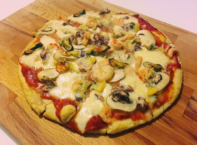 Magioni bloemkoolbodem met: tomatensaus, mozzarella, champignons en zeevruchten.
